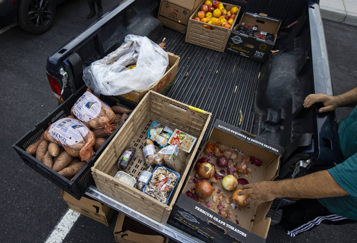People in need get donated food from Amber Stevenson at a shopping center in Las Vegas on Wedne ...