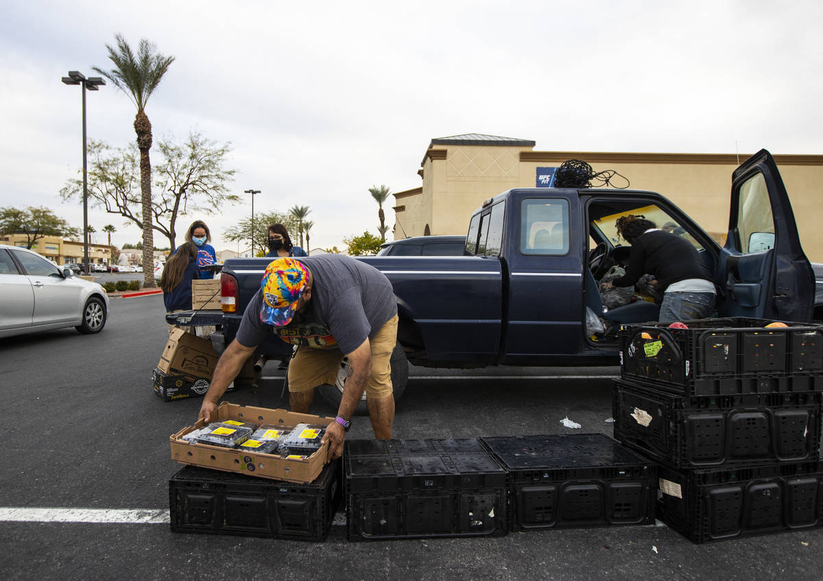 Zach Lopez, left, assists Amber Stevenson in giving out food at a shopping center in Las Vegas ...