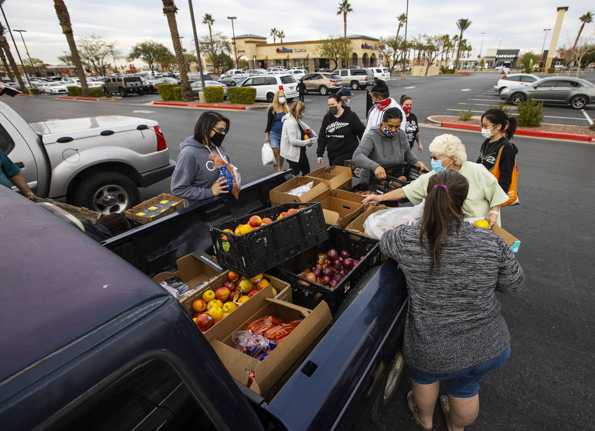 People in need get donated food from Amber Stevenson, not pictured, at a shopping center in Las ...