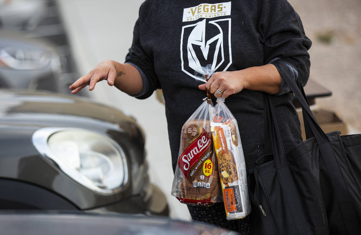 A woman gathers donated food from Amber Stevenson at a shopping center in Las Vegas on Wednesda ...