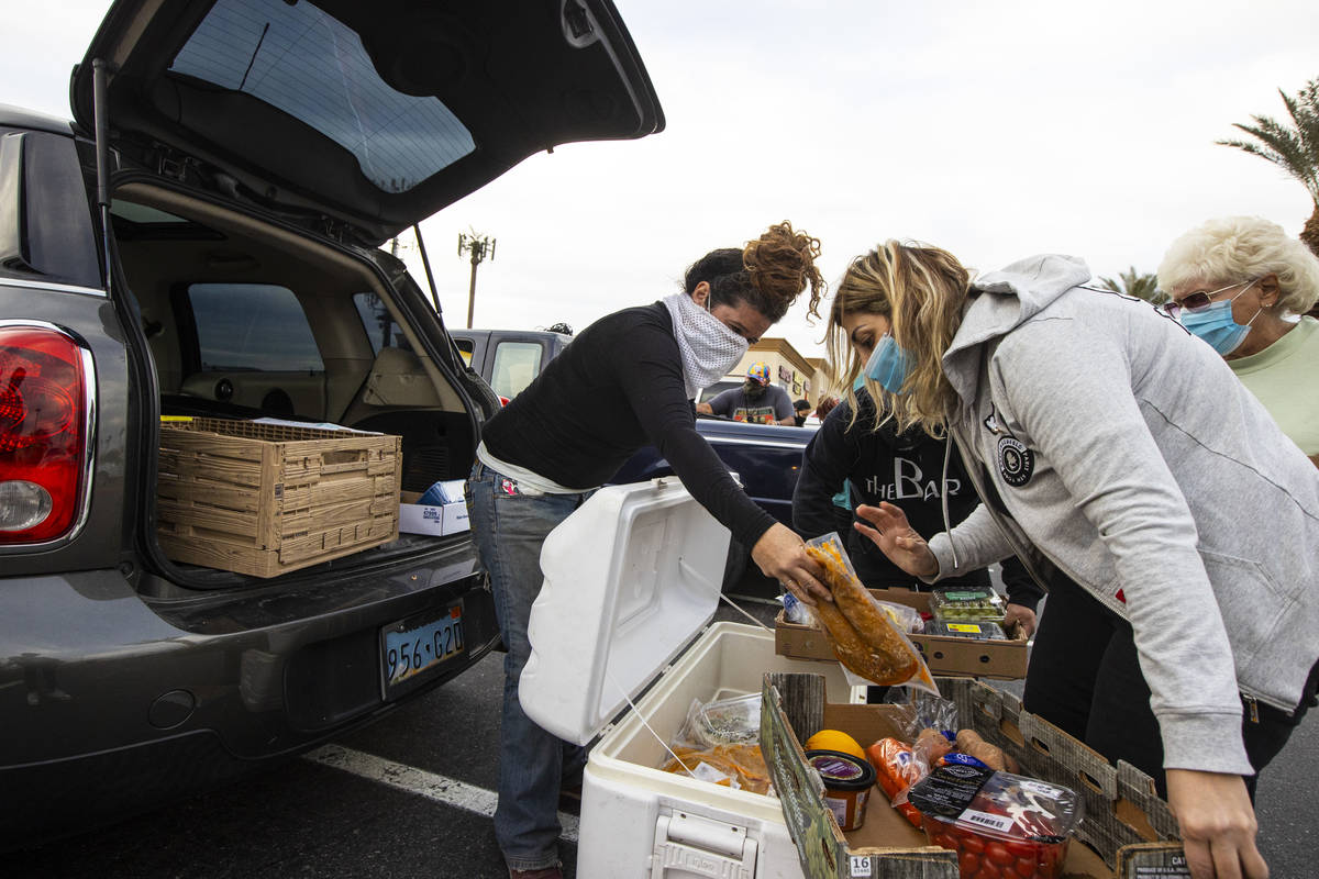 Amber Stevenson, left, hands out food to people in need at a shopping center in Las Vegas on We ...