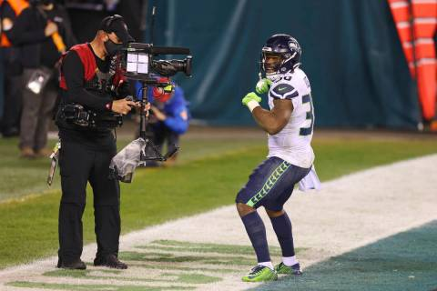 Seattle Seahawks' Carlos Hyde (30) celebrates in front of an ESPN Monday Night Football camera ...