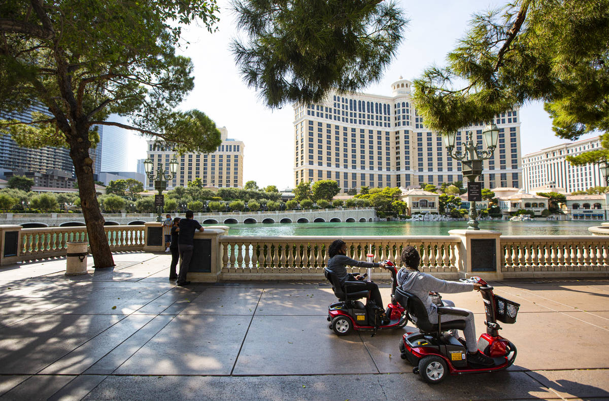 People pass by the Bellagio fountains while riding mobility scooters on the Las Vegas Strip on ...