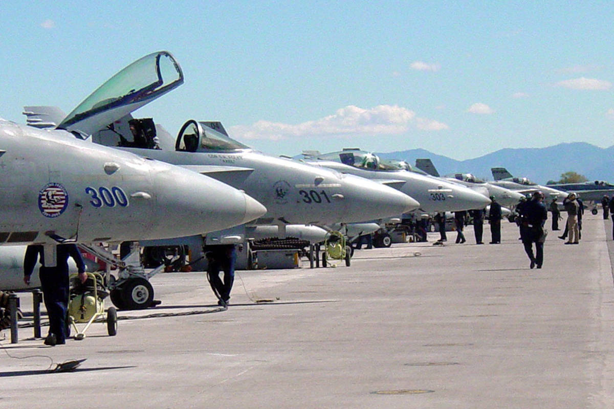 Maintenance personnel move along the flightline of F/A-18 Hornet Strike Fighter aircraft attach ...
