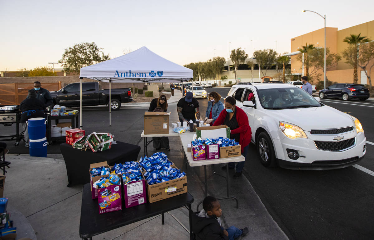 Kisha Walker, a volunteer with Liberty Baptist Church, center, prepares food and snacks to hand ...