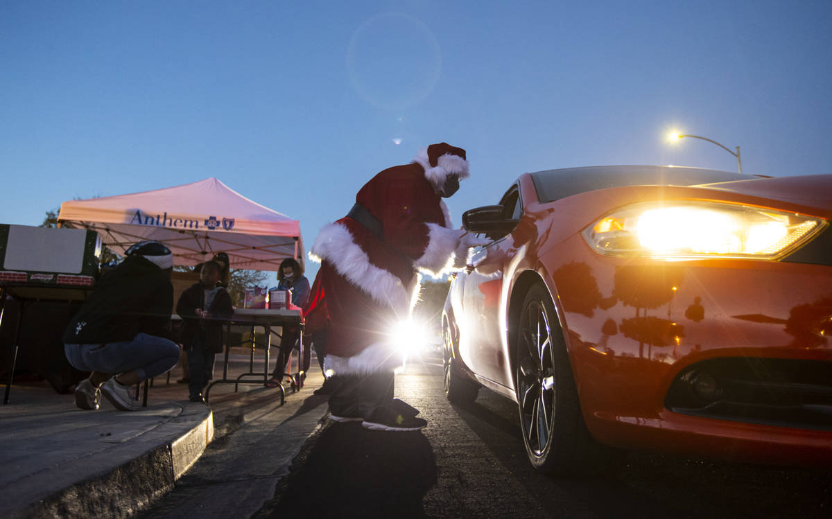 A retired Metro police captain hands out treats as part of a charity drive-thru event for famil ...