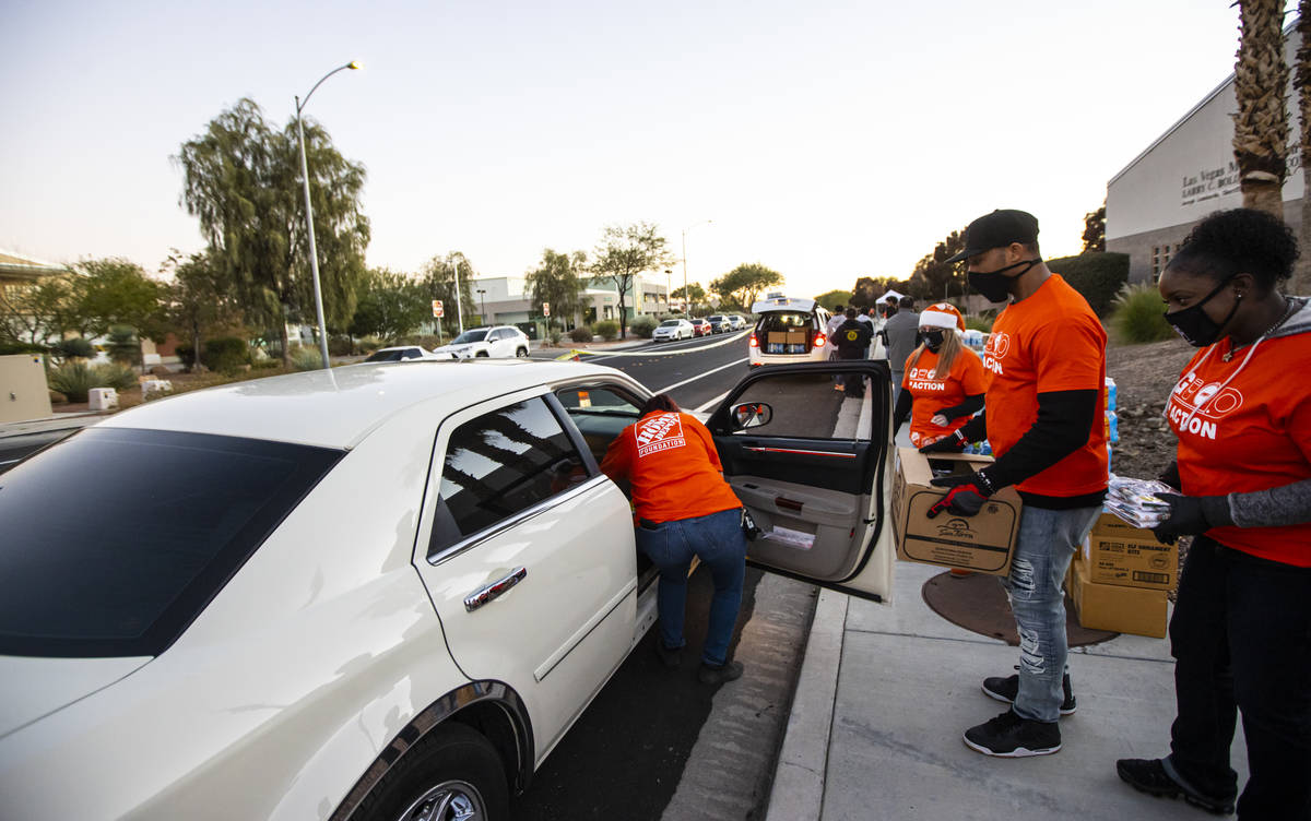 Volunteers with Home Depot deliver cases of water along with meals, holiday decorating kits, ha ...