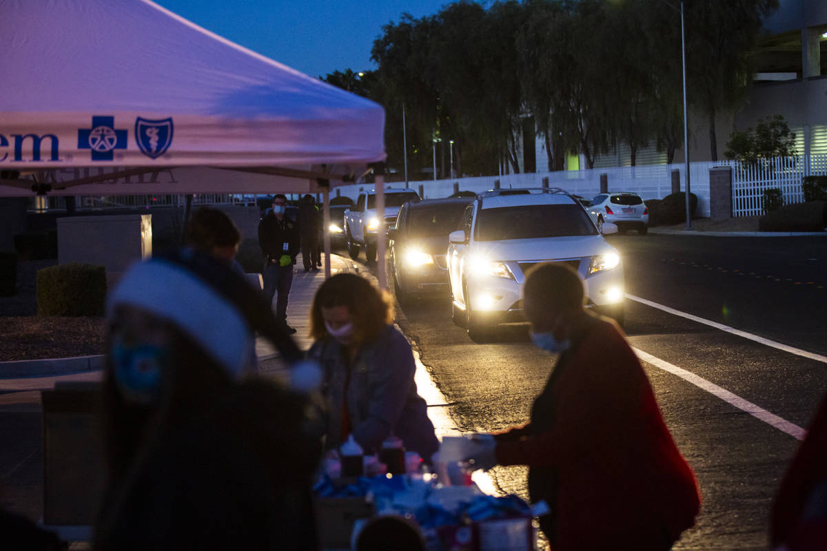 Families in need line up for a charity drive-thru event at Metroճ Bolden Area Command substati ...