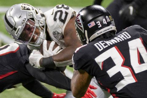 Las Vegas Raiders running back Josh Jacobs (28) is tackled by Atlanta Falcons cornerback Darque ...