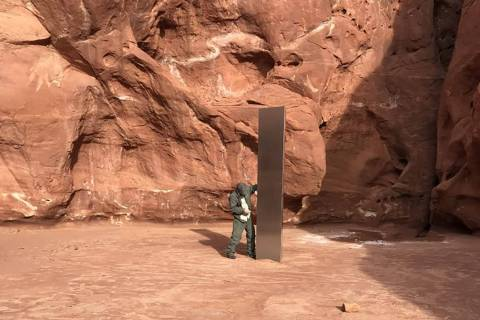 A crew member next to a metal monolith discovered Nov. 18, 2020, in a remote southeast Utah can ...