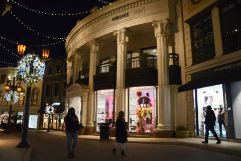 People walk near the Versace boutique on Rodeo Drive, decorated for the holidays amid the coron ...