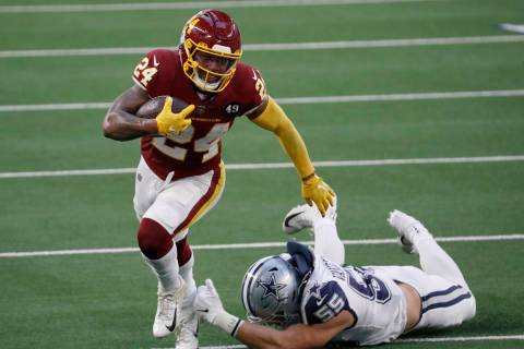 Washington Football Team running back Antonio Gibson (24) escapes a tackle attempt by Dallas Co ...