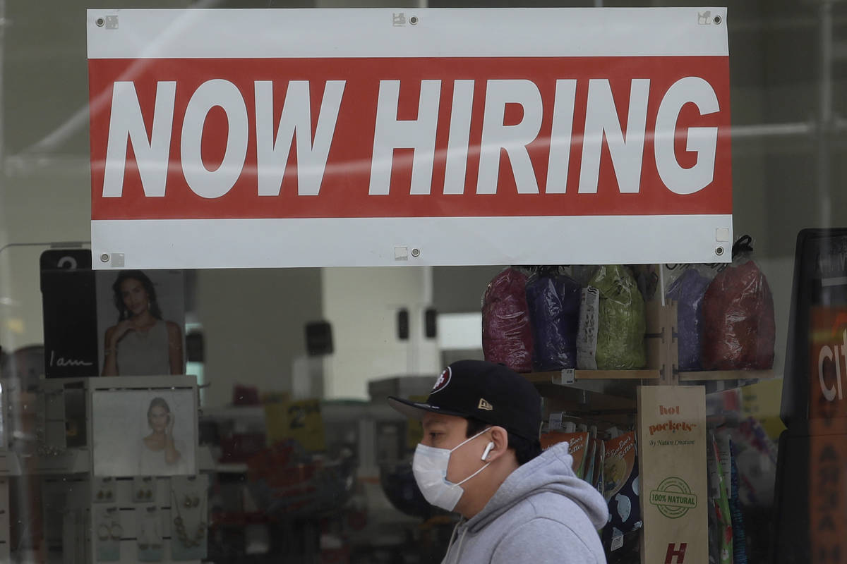 FILE - This May 7, 2020, file photo shows a man wearing a mask while walking under a Now Hiring ...