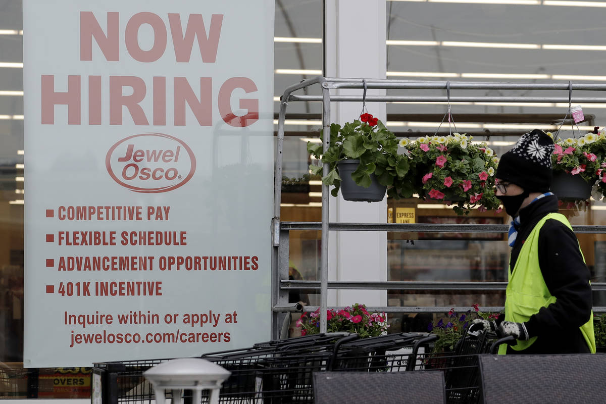 A man pushes carts as a hiring sign shows at a Jewel Osco grocery store in Deerfield, Ill., Thu ...