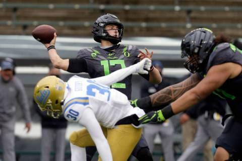 Oregon's Tyler Shough throws down field under pressure from UCLA's Elisha Guidry during the sec ...