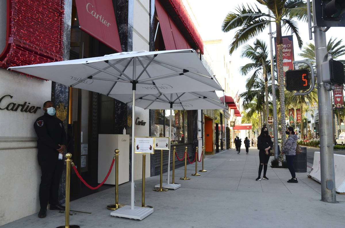 A security guard in a face mask stands outside Cartier jewelry shop with no customers on line d ...