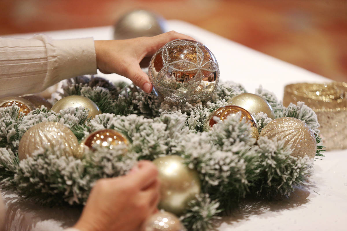 Sylvia Sanchez of Brownsville, Texas, works on her wreath during the Mastering Holiday Wreaths ...