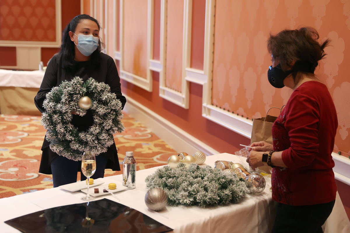 Evelyn Herrera, assistant director of horticulture and floral, assists Addie Carpio of Las Vega ...