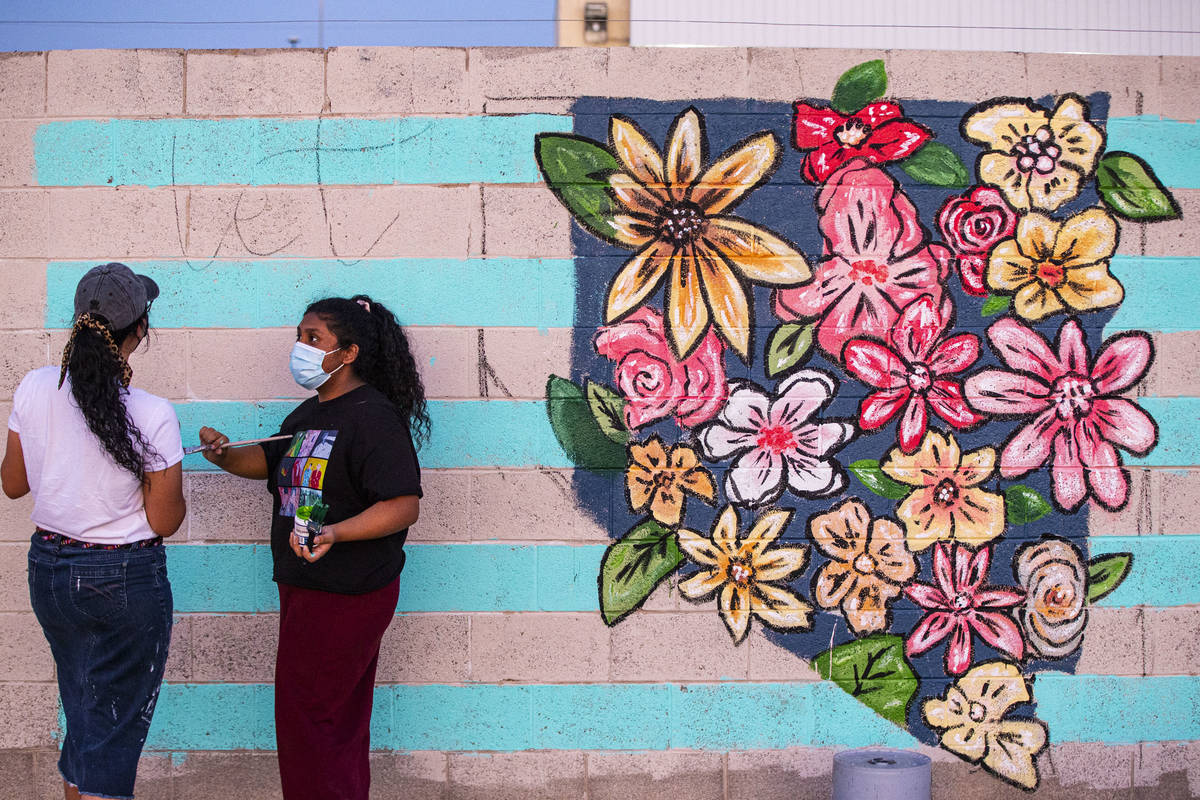 Artists Angie Castillo, left, and Vivian Avila work on a mural at the site of the former Moulin ...