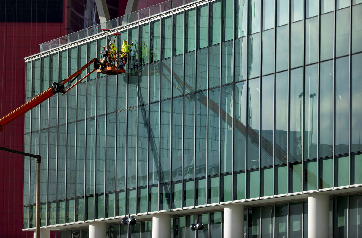 Workers clean the windows out front as construction continues about the new Las Vegas Conventio ...