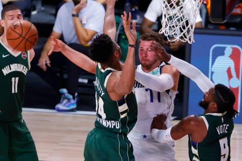 Dallas Mavericks' Luka Doncic passes away from Milwaukee Bucks' Giannis Antetokounmpo (34) and ...
