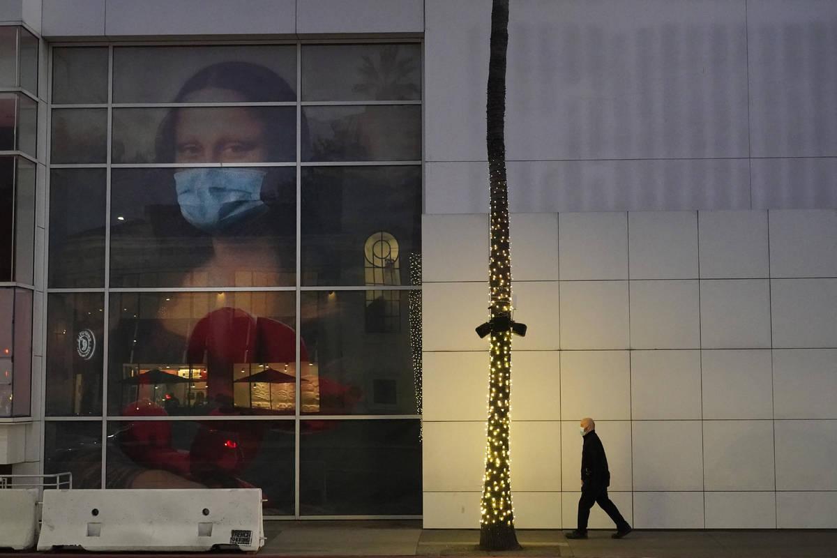 A masked pedestrian walks past of a COVID 19-themed mural depicting Leonardo da Vinci's Mona Li ...