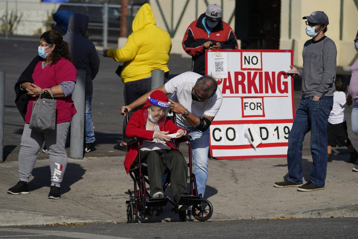 People wait in line on the sidewalk for a free COVID-19 test outside the Echo Park branch of th ...