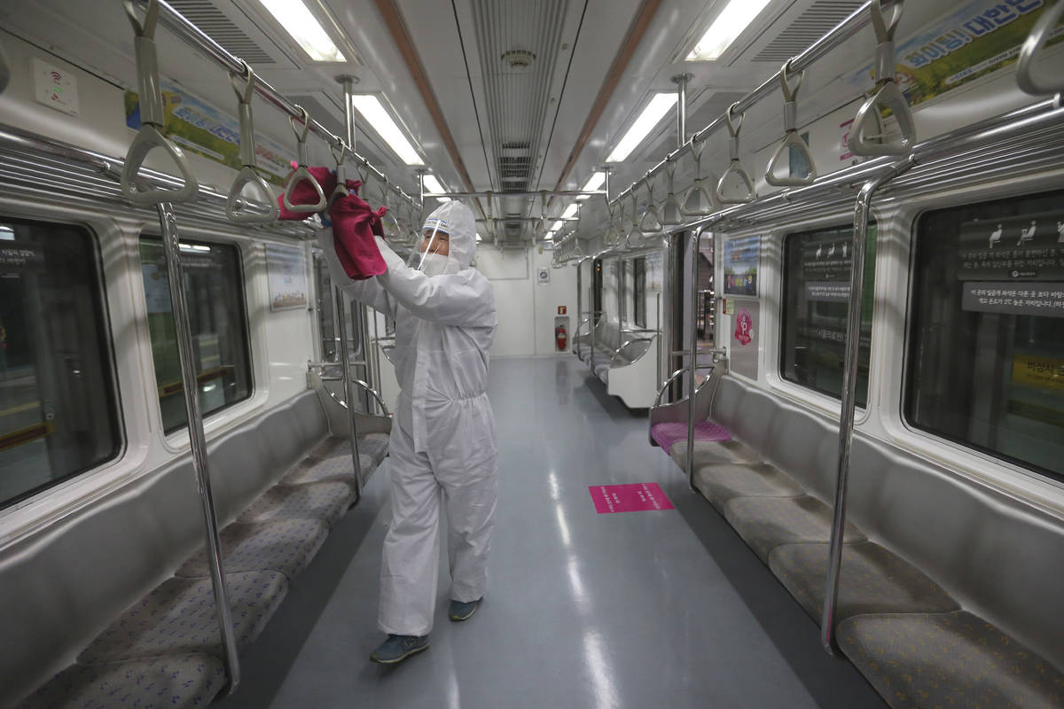 An employee disinfects handles as a precaution against the coronavirus on a subway train at a s ...