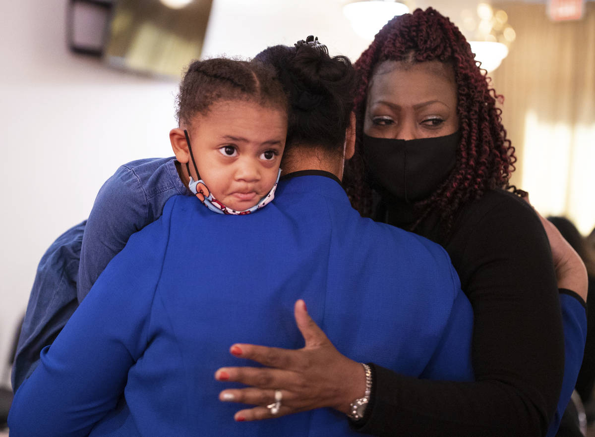 Carolyn Dauphine, right, consoles Evelini Gibbs and Tiye Egypt, 2, during a memorial service fo ...