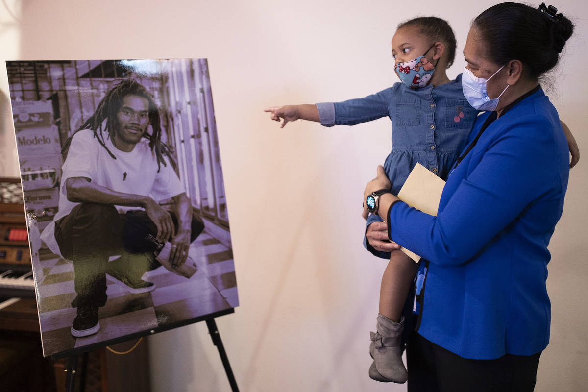 June Atkins, right, mother of Genesis Atkins, holds Tiye Egypt, 2, as she points at a photo of ...