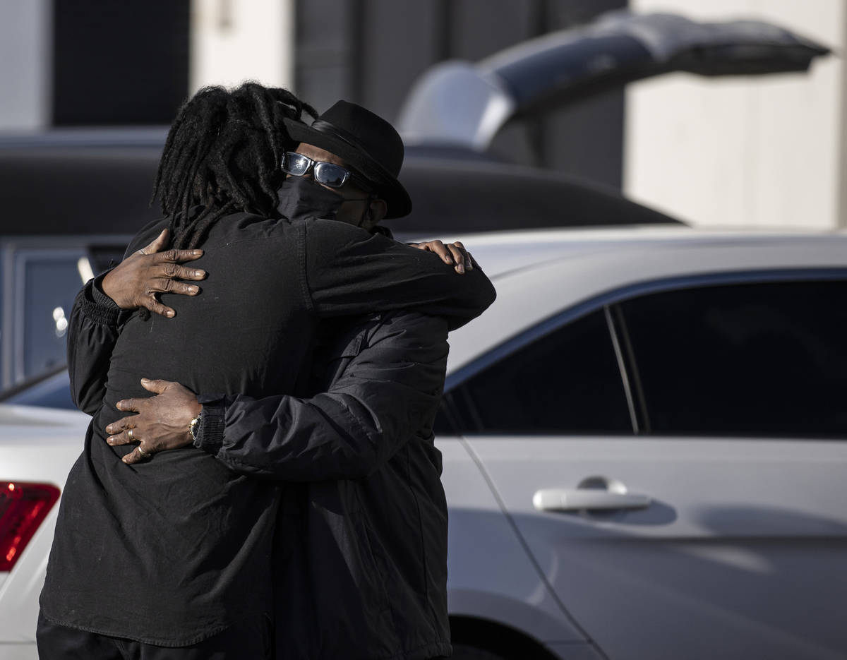 Steve Atkins, right, hugs his son Ace Atkins outside Hites Funeral Home and Crematory during a ...