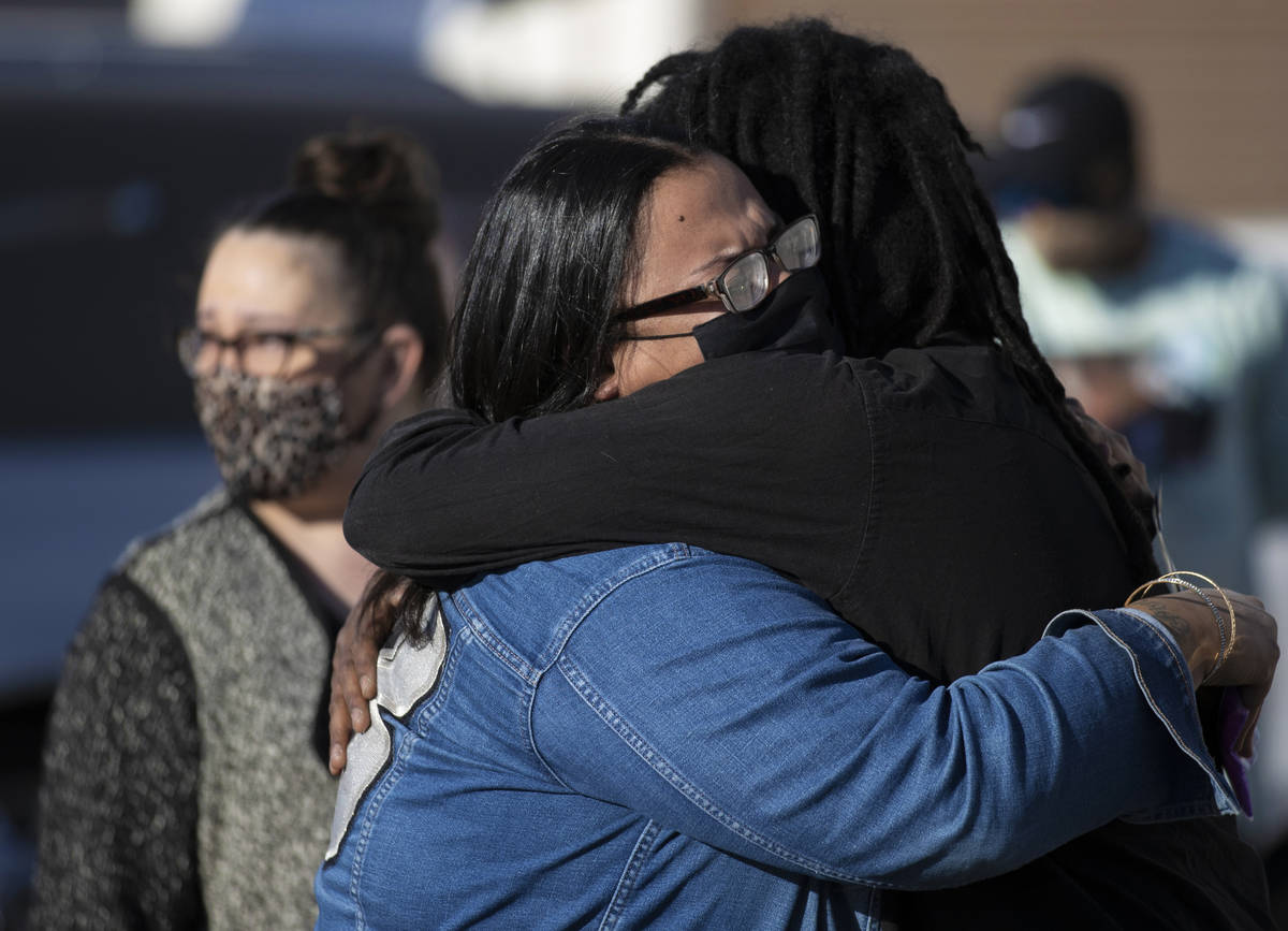 Friends and family grieve outside Hites Funeral Home and Crematory during a memorial service fo ...