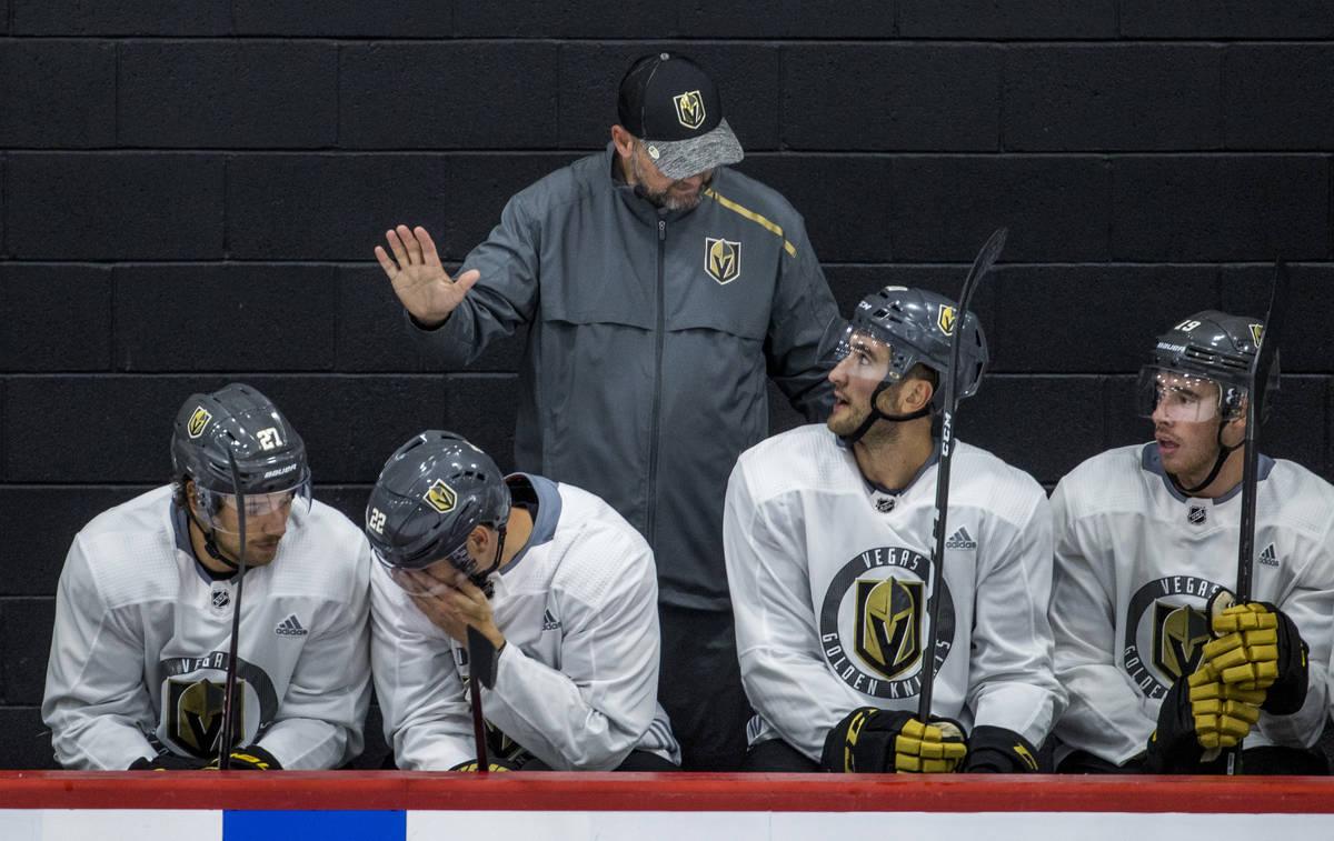 Vegas Golden Knights head coach Peter DeBoer, above, instructs center Nicolas Roy (10, below) a ...
