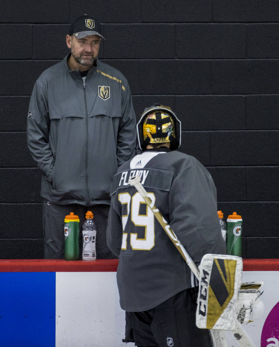 Vegas Golden Knights head coach Peter DeBoer listens to goaltender Marc-Andre Fleury (29) duri ...