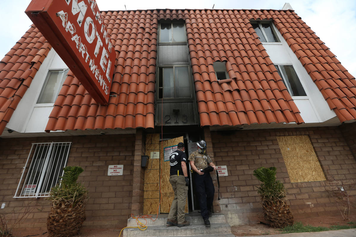 Employees with the Forensic Investigations Group work inside the Alpine Motel during an investi ...
