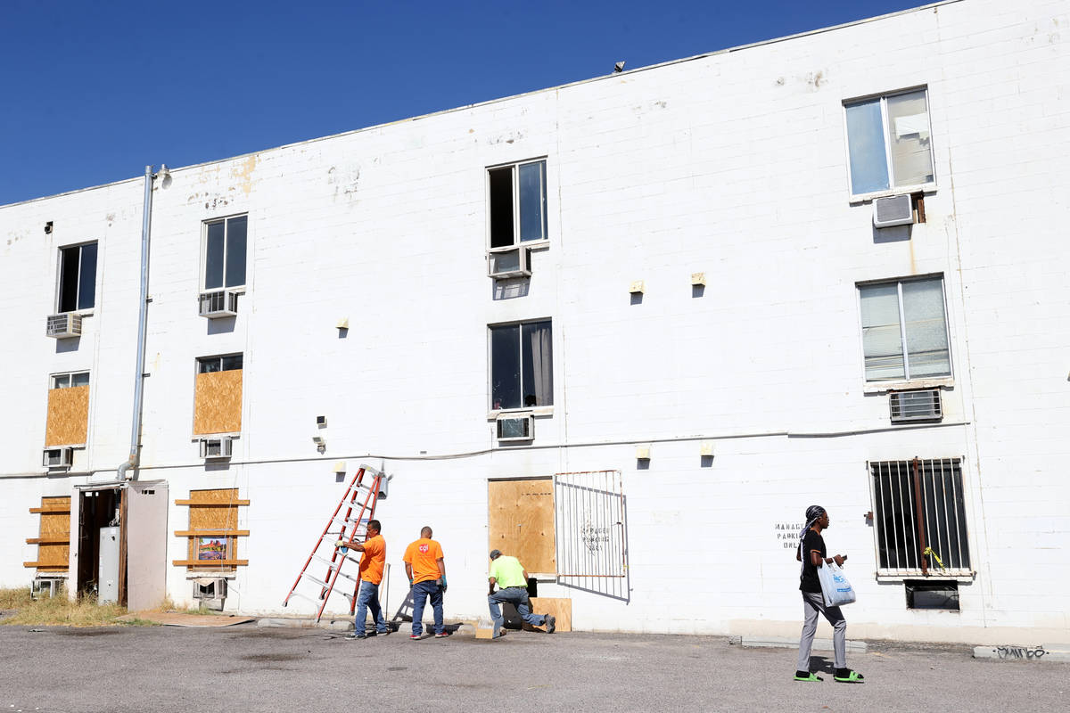 Workers board up windows at the Alpine Motel Apartments in downtown Las Vegas Thursday, Oct. 15 ...