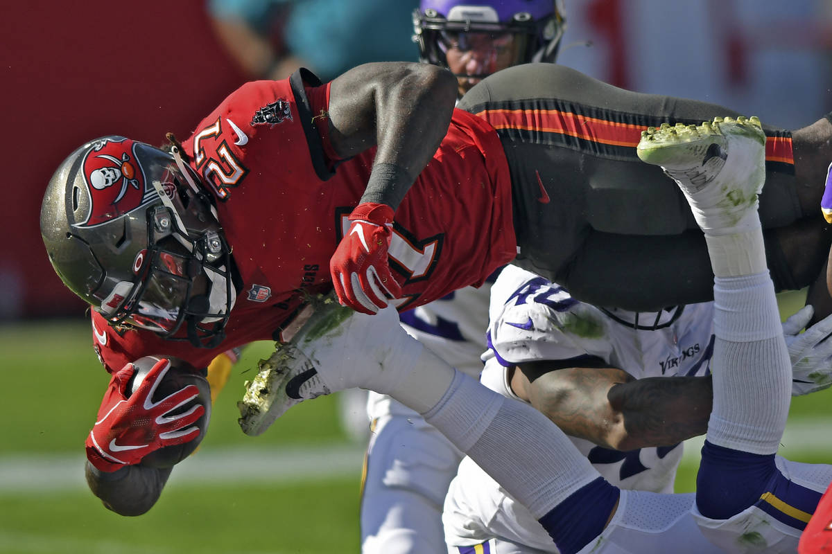 Tampa Bay Buccaneers running back Ronald Jones II (27) dives over the line to score on a 1-yard ...