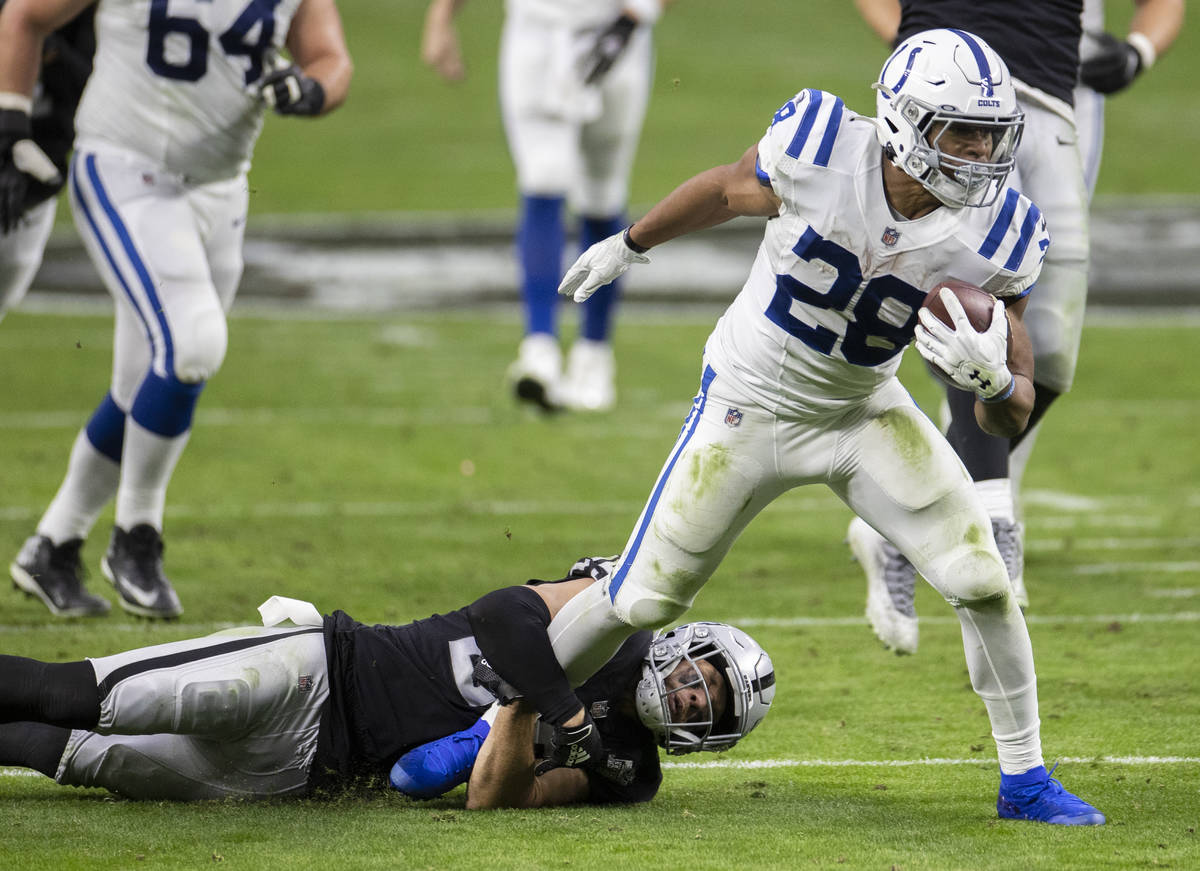 Indianapolis Colts running back Jonathan Taylor (28) fights for extra yardage as Raiders strong ...
