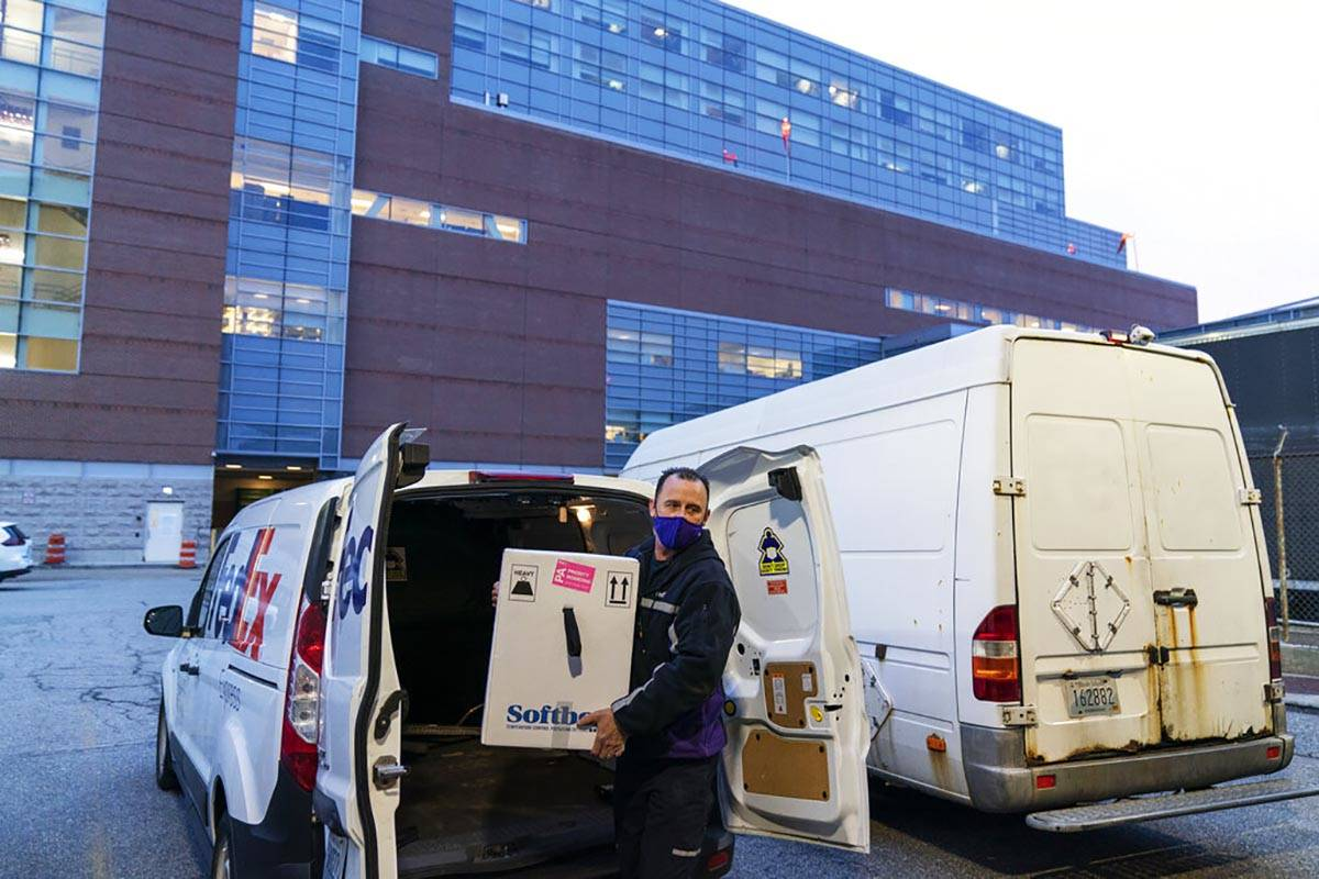 A FedEx driver delivers a box containing the Pfizer-BioNTech COVID-19 vaccine to Rhode Island H ...