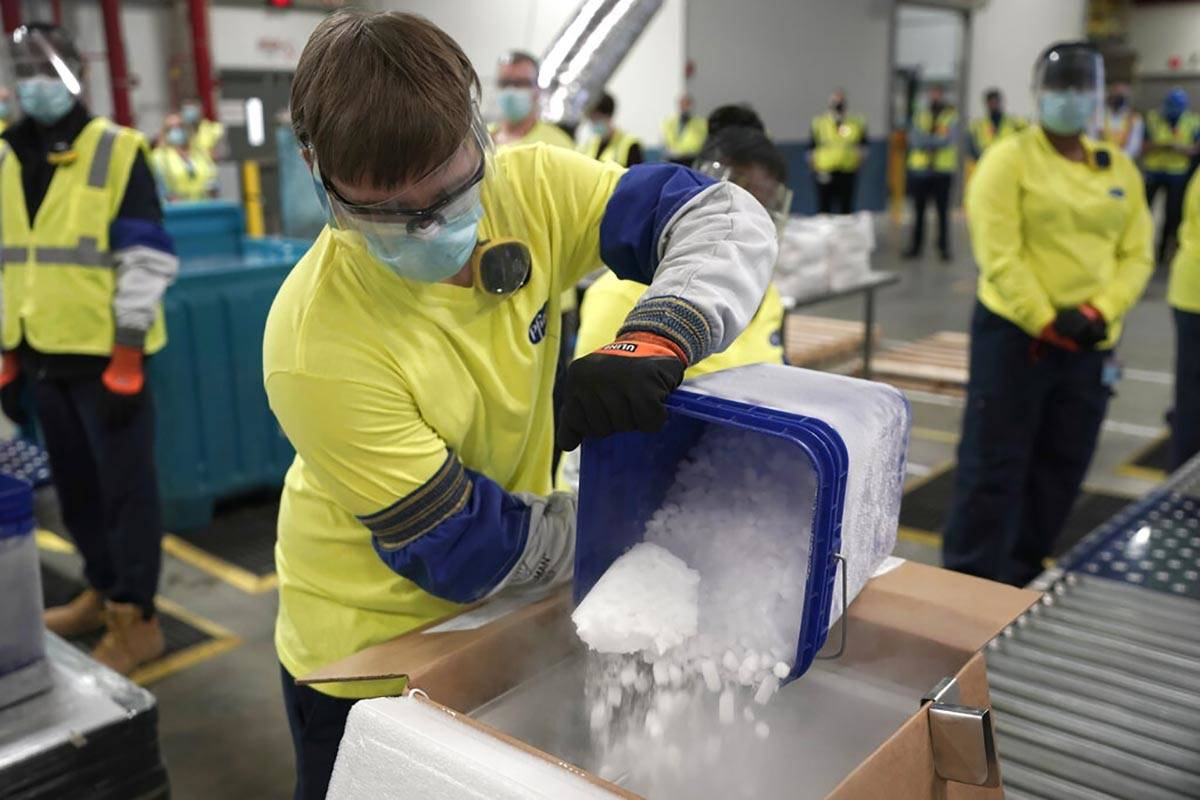 Dry ice is poured into a box containing the Pfizer-BioNTech COVID-19 vaccine as it is prepared ...