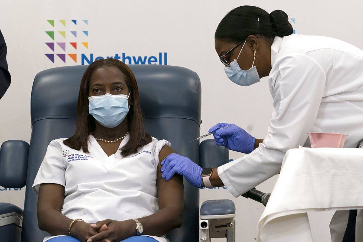 Sandra Lindsay, left, a nurse at Long Island Jewish Medical Center, is inoculated with the Pfiz ...