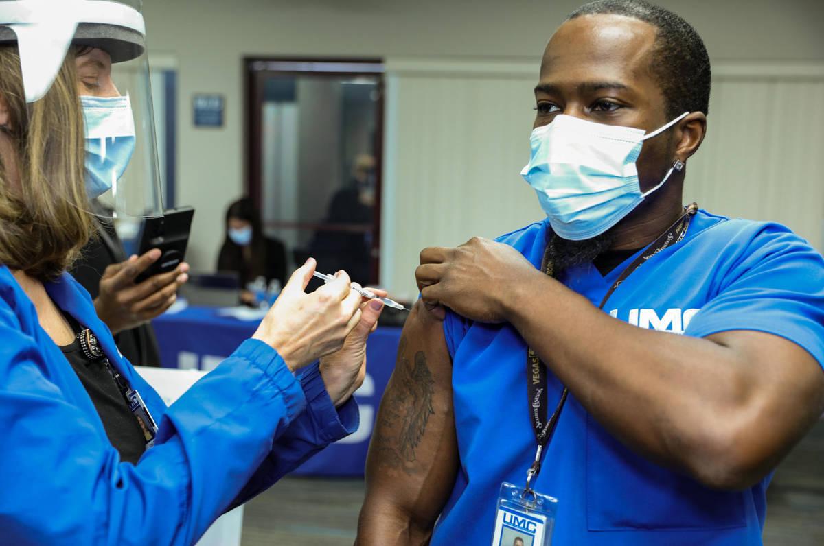 University Medical Center Employee Health Nurse Lori Conti administers a COVID-19 vaccine to UM ...