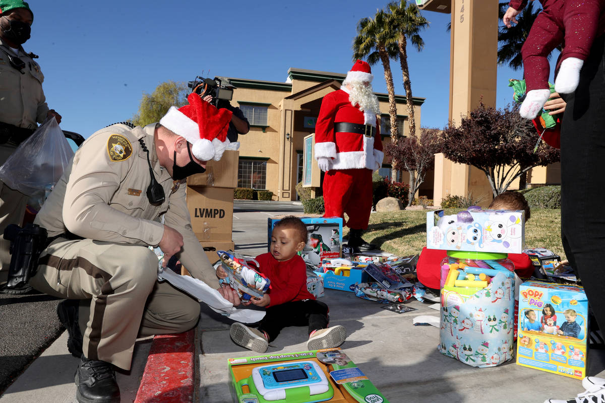 Las Vegas police officer Mike Sian watches Adriel Stephens, 1, open gifts during the Metropolit ...