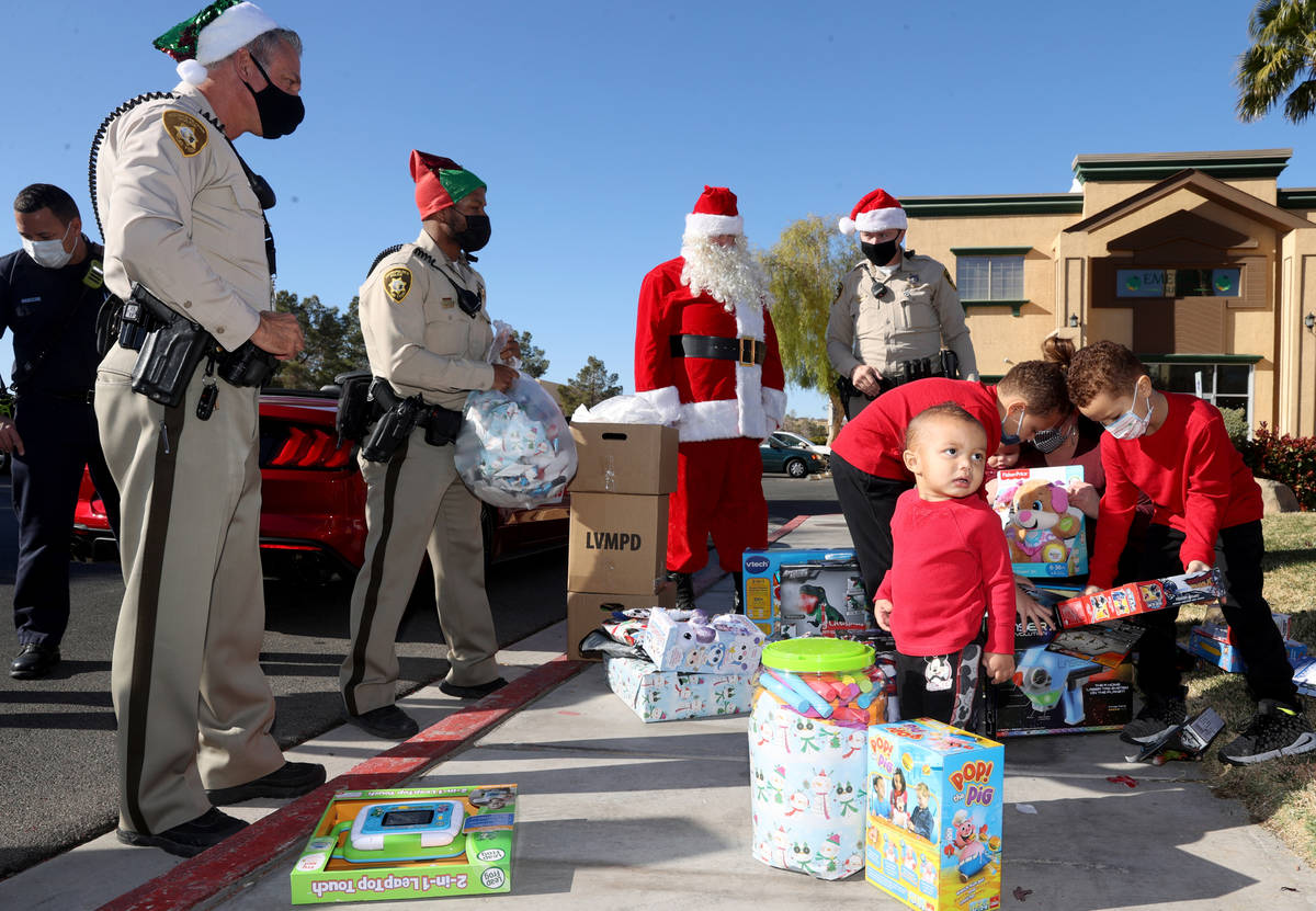 Las Vegas police officers, from left, Tommy Howell, Shadaevon Florial, Santa and Mike Sian watc ...