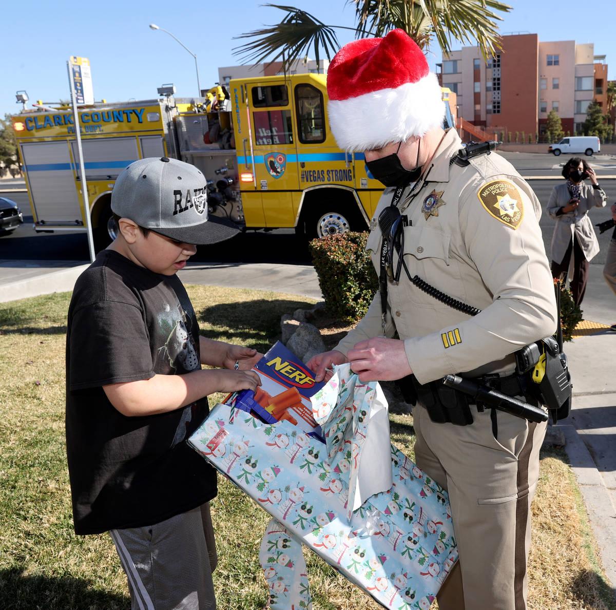 Las Vegas police officer Josh Irwin helps Kevin Salazar, 8, open gifts during the Metropolitan ...