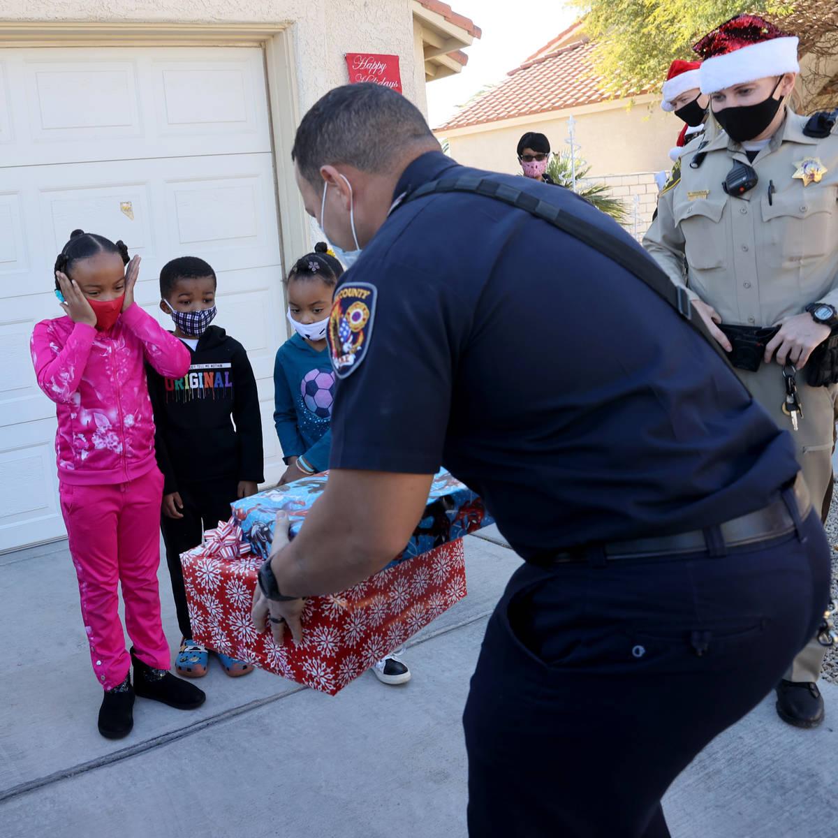 Clark County firefighter Calvin Dean and Las Vegas police officer Meike Dangervil deliver gifts ...