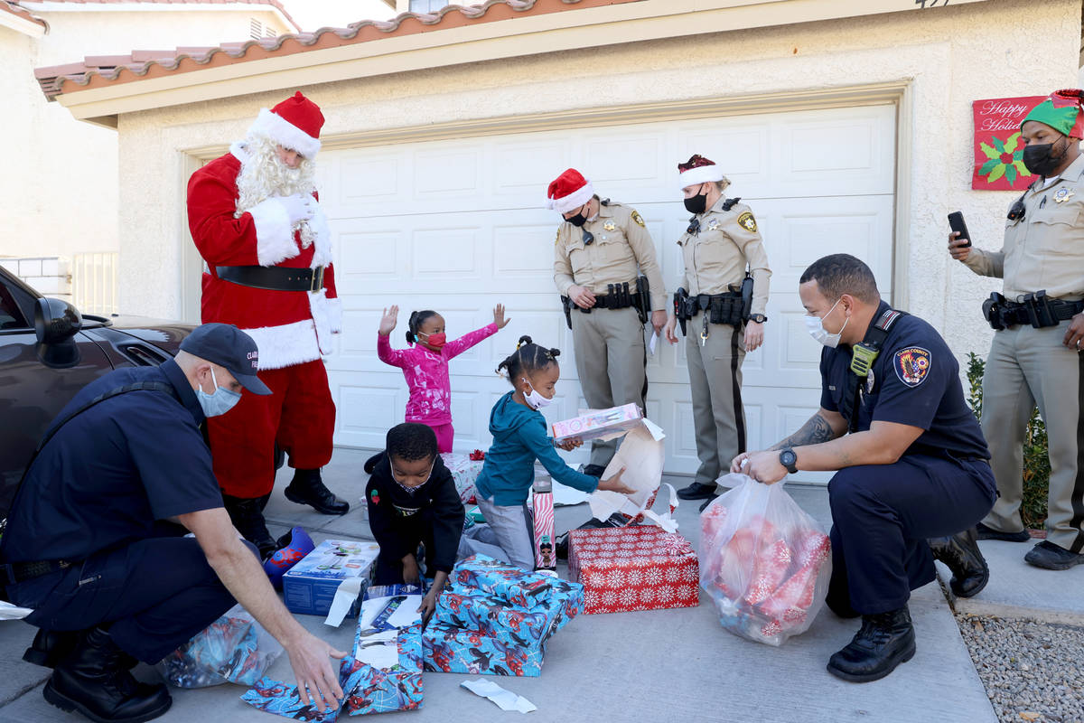 Siblings, from left, Campbell, 6 Samantha, 8, and Lela Snipes 8, open gifts during the Metropol ...