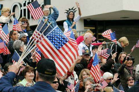 People wave flags at veterans as they watch the Las Vegas Veterans Day Parade. (Las Vegas Revie ...
