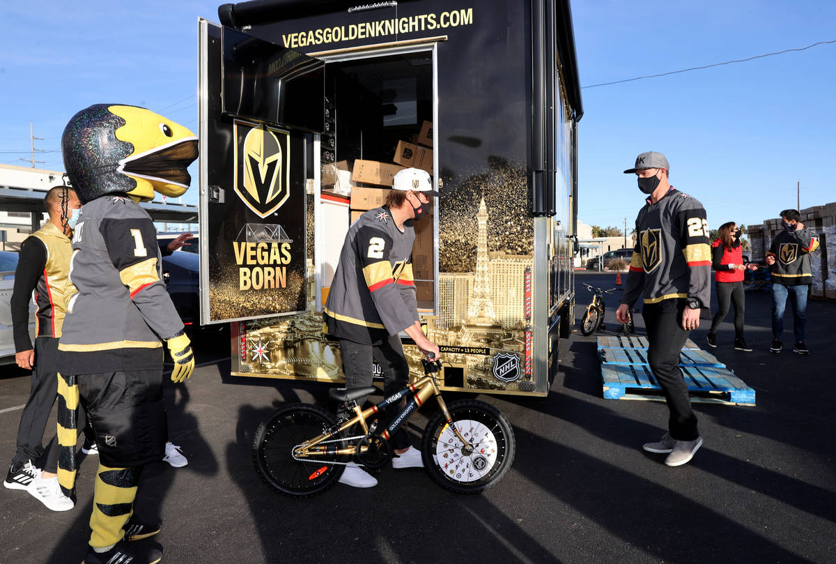 Golden Knights players Zach Whitecloud, from left, Nick Holden and Max Pacioretty unload bikes ...