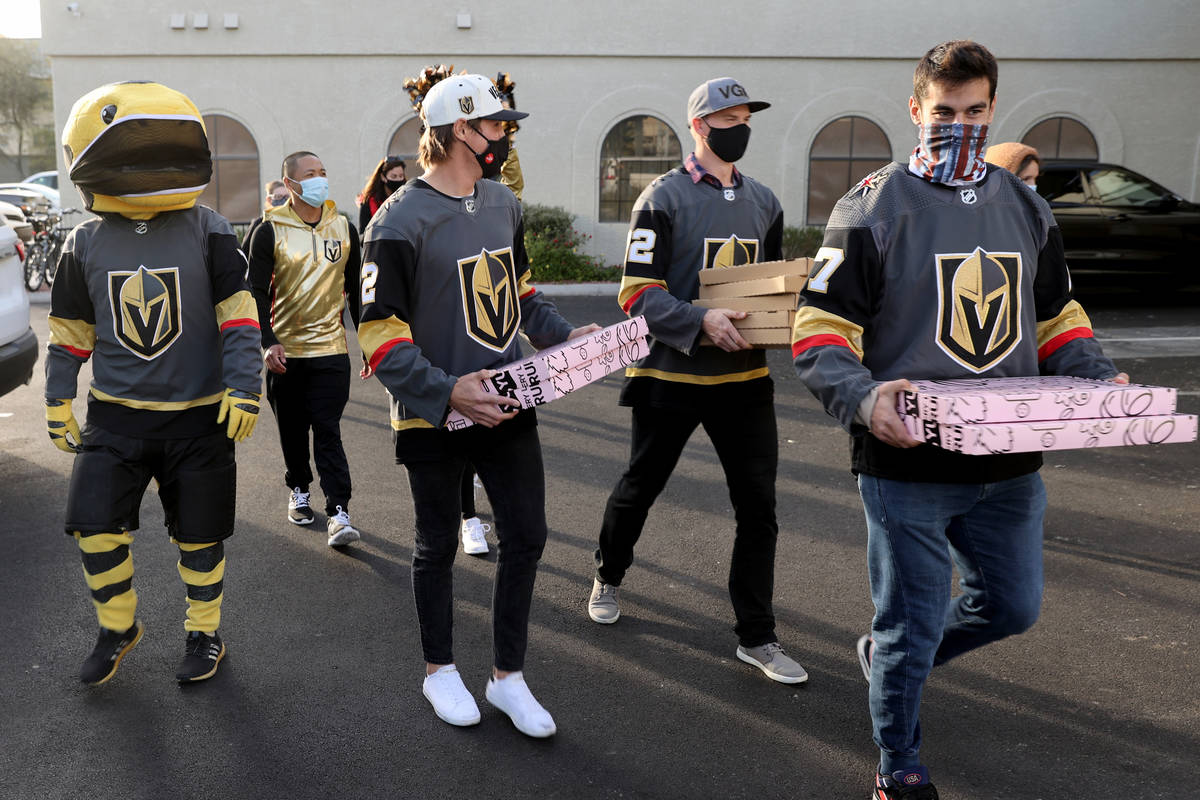 Golden Knights players Max Pacioretty, from right, Nick Holden and Zach Whitecloud load pizzas ...